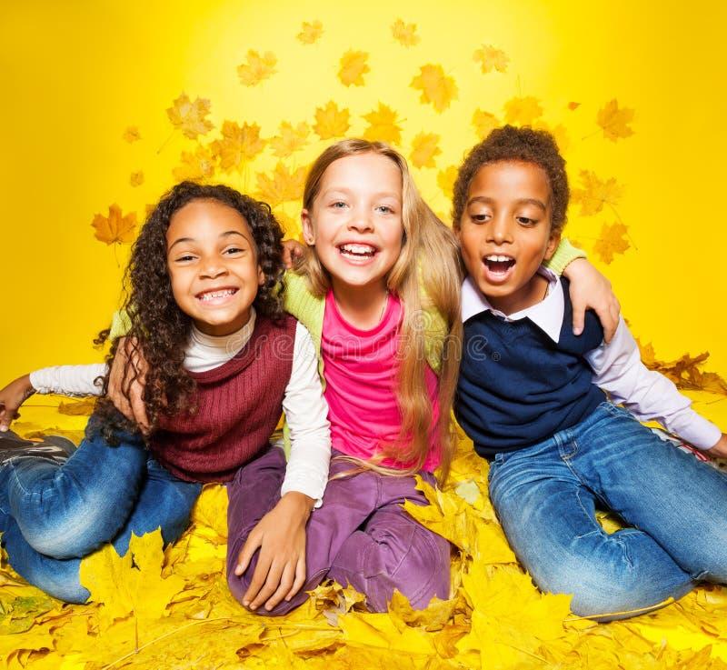 Tres amigos felices en las hojas de arce imagen de archivo libre de regalías