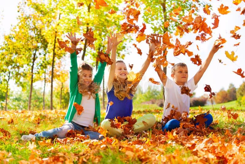 Tres amigos felices que juegan con las hojas lanzadas fotos de archivo