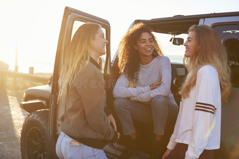 Tres amigos femeninos jovenes en un viaje por carretera que hablan al lado del coche imagen de archivo libre de regalías