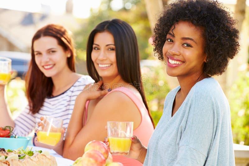 Tres amigos femeninos que disfrutan de la comida en el partido al aire libre fotografía de archivo