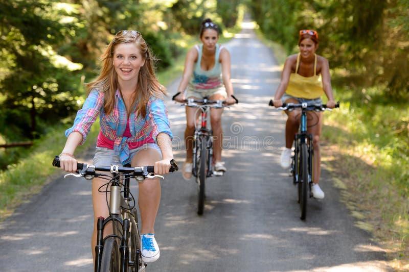 Tres amigos femeninos que montan las bicis en parque fotografía de archivo libre de regalías
