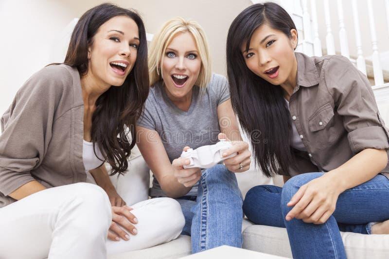 Tres amigos hermosos de las mujeres que juegan a los videojuegos en casa imagen de archivo