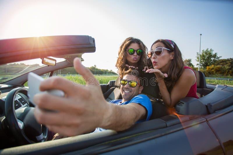 Tres amigos hermosos jovenes que toman una imagen del selfie en un coche convertible imagen de archivo