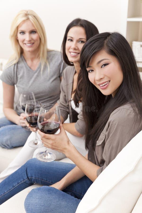 Tres amigos interraciales de las mujeres que beben el vino imagenes de archivo