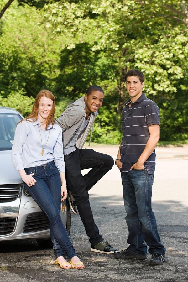 Tres amigos jovenes con un coche fotografía de archivo libre de regalías