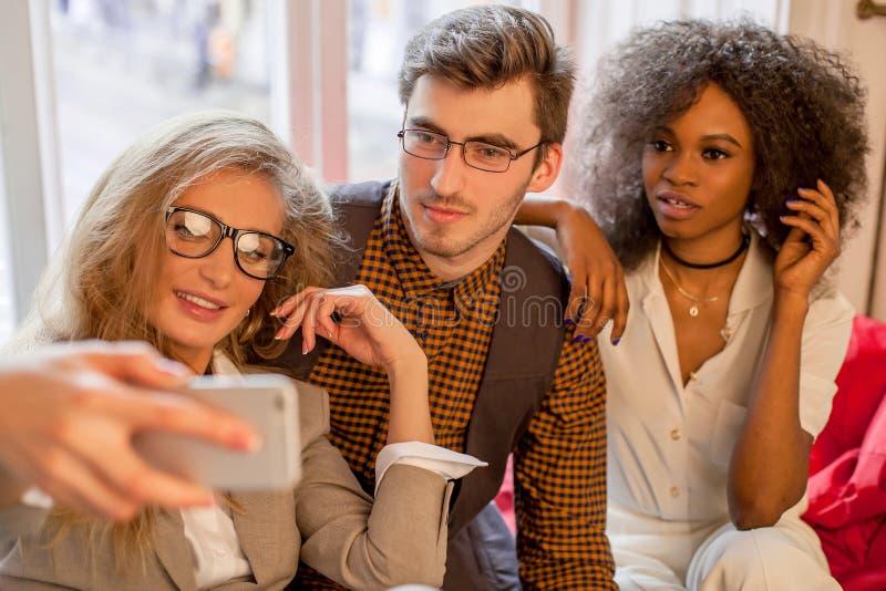 Tres amigos jovenes en negocio visten hacer el selfie en su oficina imagen de archivo