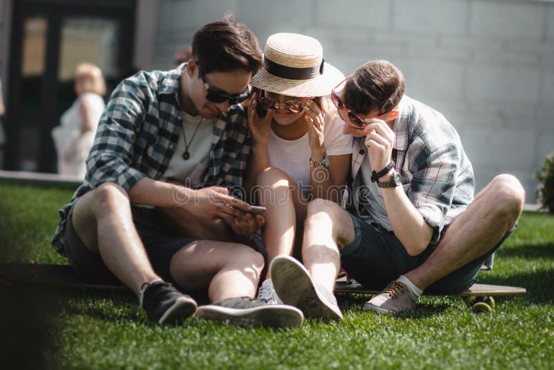 Tres amigos jovenes se están sentando en el aire libre de la hierba y están mirando el teléfono móvil imagen de archivo