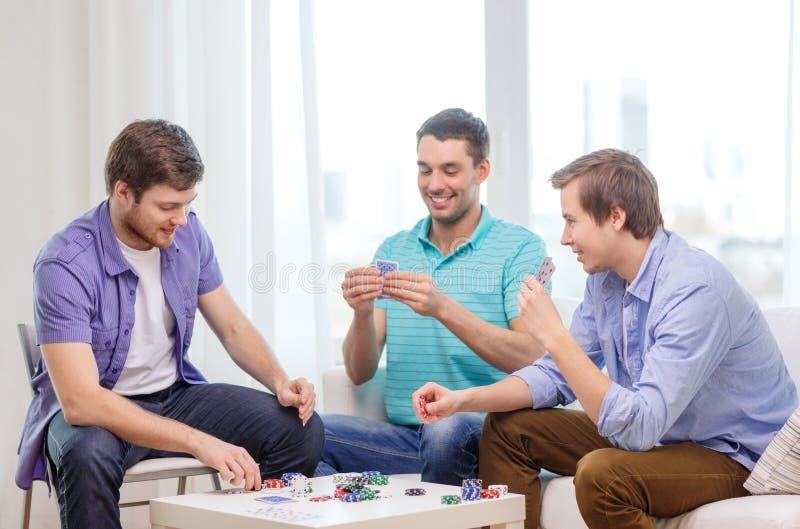 Tres amigos masculinos felices que juegan el póker en casa imagenes de archivo