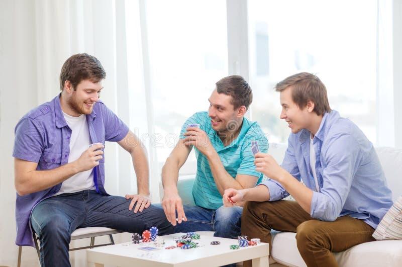Tres amigos masculinos felices que juegan el póker en casa foto de archivo