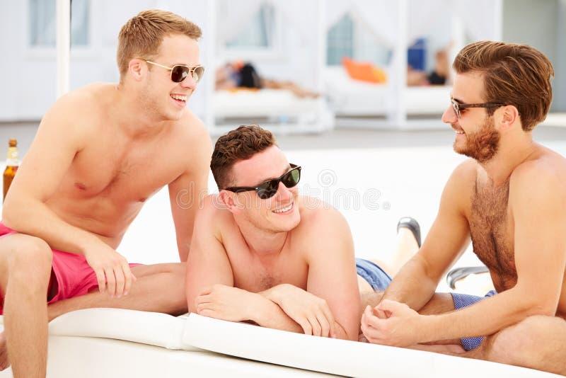 Tres amigos masculinos jovenes el día de fiesta por la piscina junto imagen de archivo libre de regalías