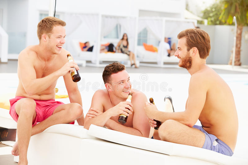 Tres amigos masculinos jovenes el día de fiesta por la piscina junto fotos de archivo