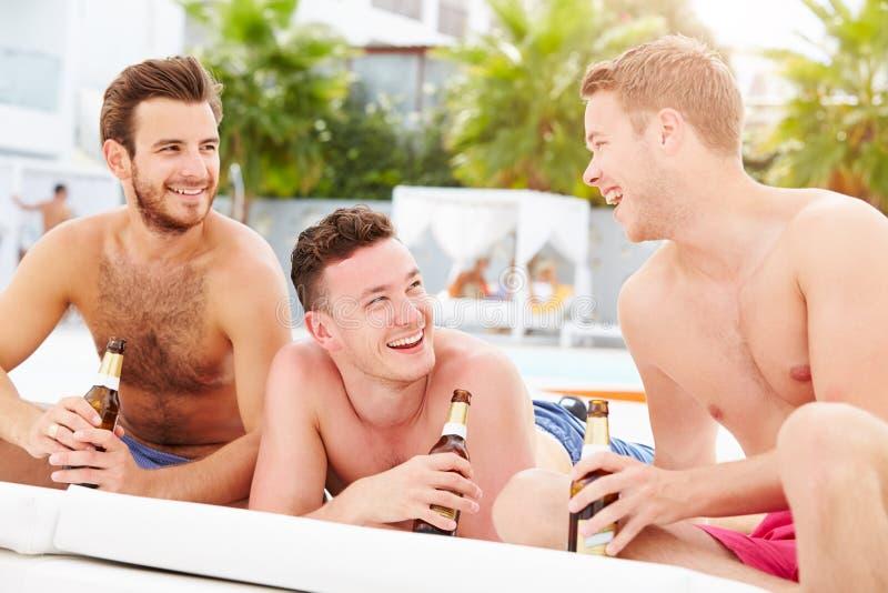 Tres amigos masculinos jovenes el día de fiesta por la piscina junto fotografía de archivo