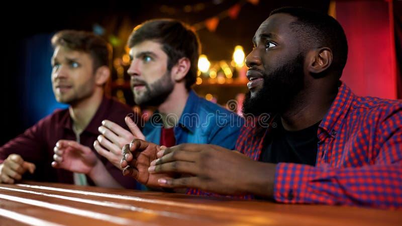 Tres amigos multiétnicos que miran competencia de la canción en la TV en barra, alistan para el aplauso imagenes de archivo