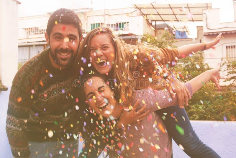 Tres amigos muy felices en el partido del tejado y el confeti que lanza imágenes de archivo libres de regalías