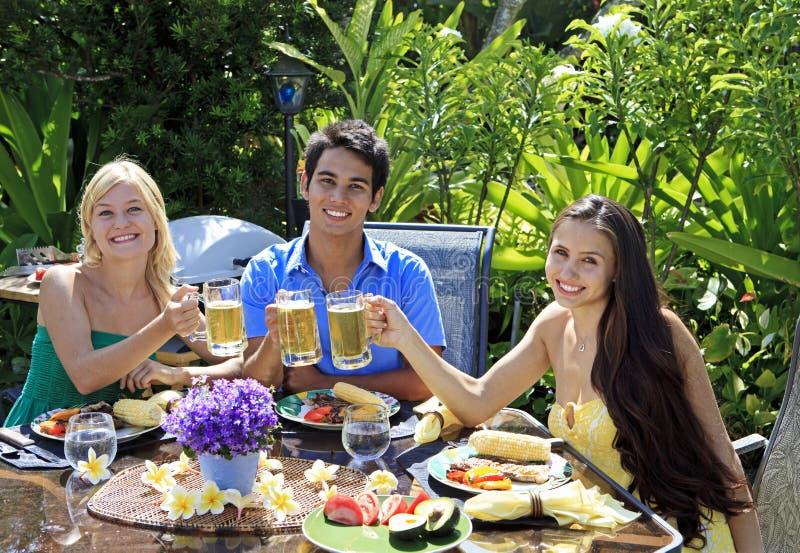 Tres amigos que almuerzan la barbacoa fotos de archivo