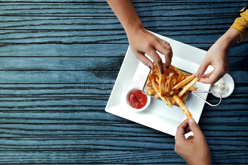 Tres amigos que comen las fritadas francesas de la patata, desempeñan servicios en el metal Mesh Flying Sieve con la salsa de inm foto de archivo libre de regalías