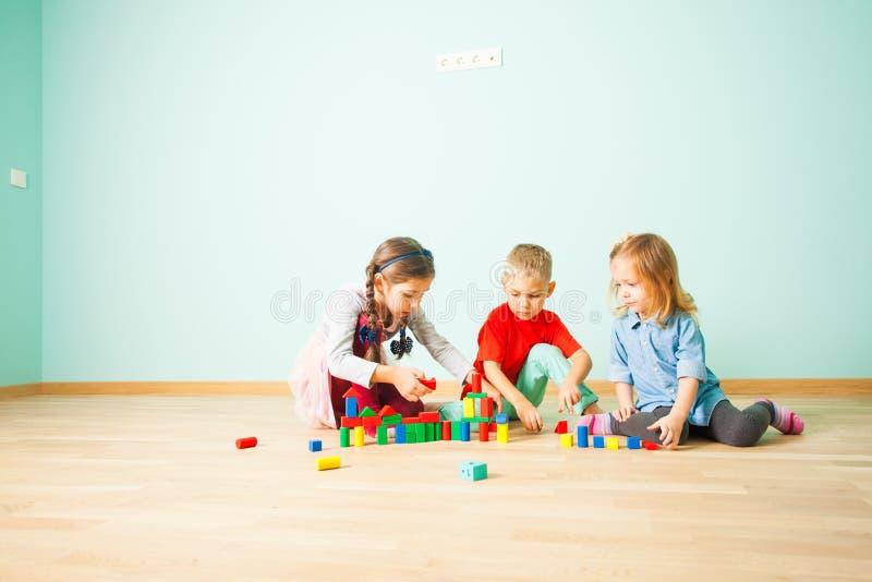 Tres amigos que construyen con los bloques en un piso fotos de archivo libres de regalías