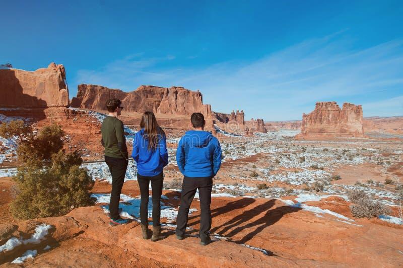 Tres amigos que disfrutan de la opinión de parque nacional de los arcos imagen de archivo libre de regalías