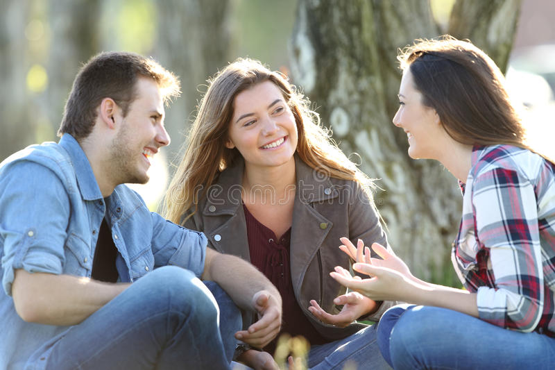 Tres amigos que hablan sentarse en un parque fotos de archivo