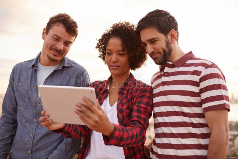 Tres amigos que miran una tableta foto de archivo libre de regalías