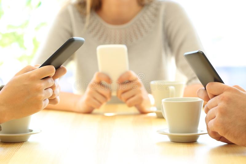 Tres amigos que usan sus teléfonos elegantes en una barra imágenes de archivo libres de regalías