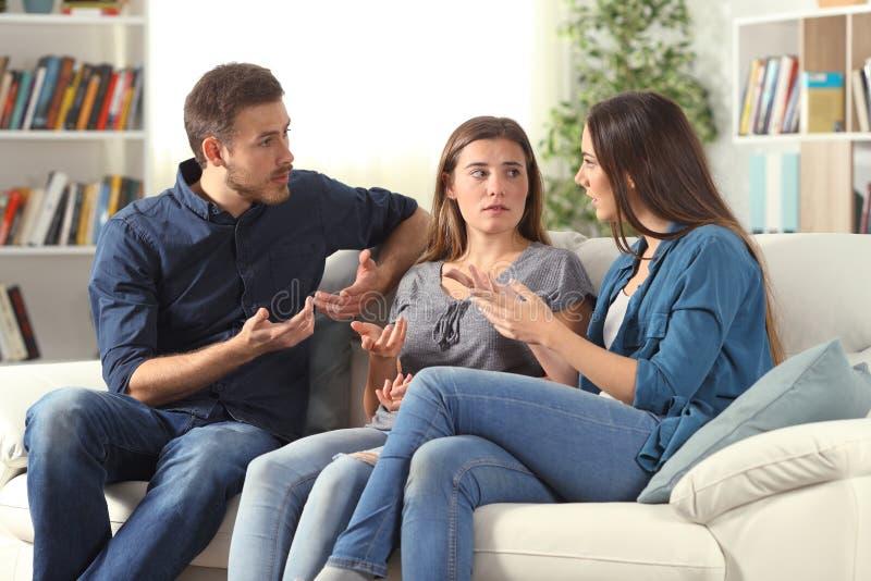 Tres amigos serios que hablan la sentada en un sof? en casa imagen de archivo
