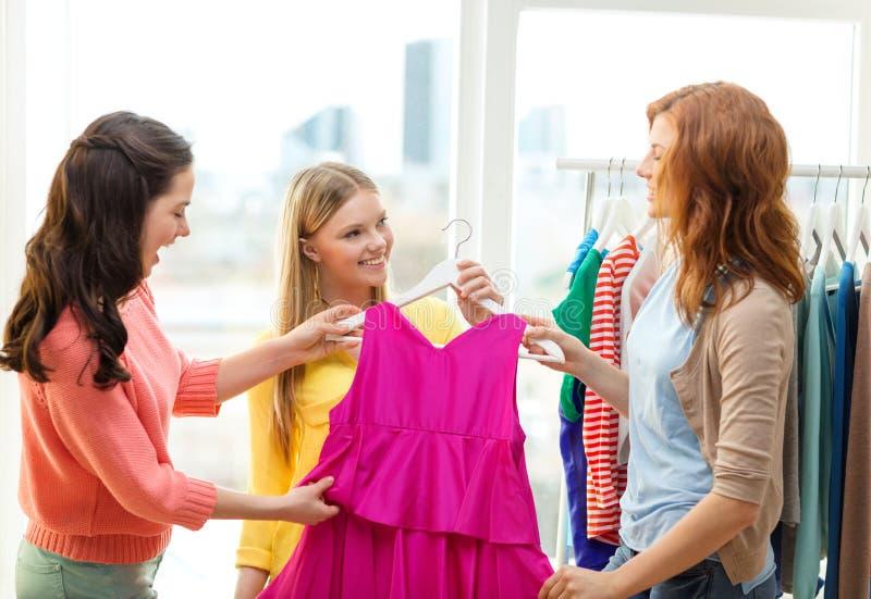 Tres amigos sonrientes que intentan en un poco de ropa imágenes de archivo libres de regalías