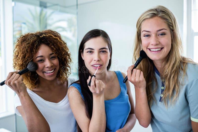 Tres amigos sonrientes que ponen maquillaje junto imagen de archivo libre de regalías