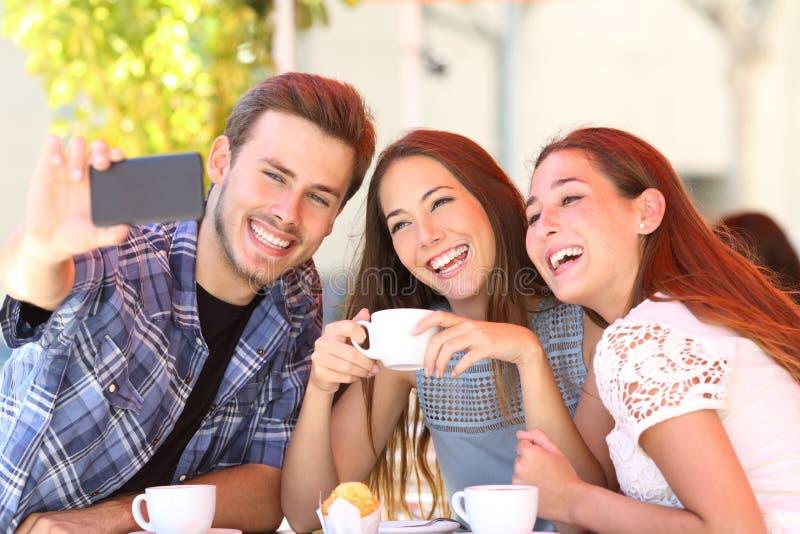 Tres amigos sonrientes que toman selfies en una cafetería fotografía de archivo