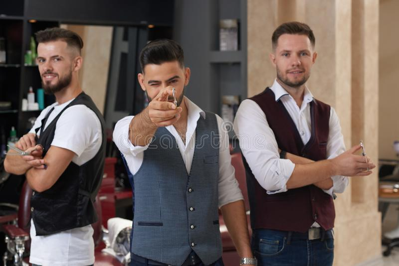 Tres amos que presentan con las tijeras en barbería imagenes de archivo