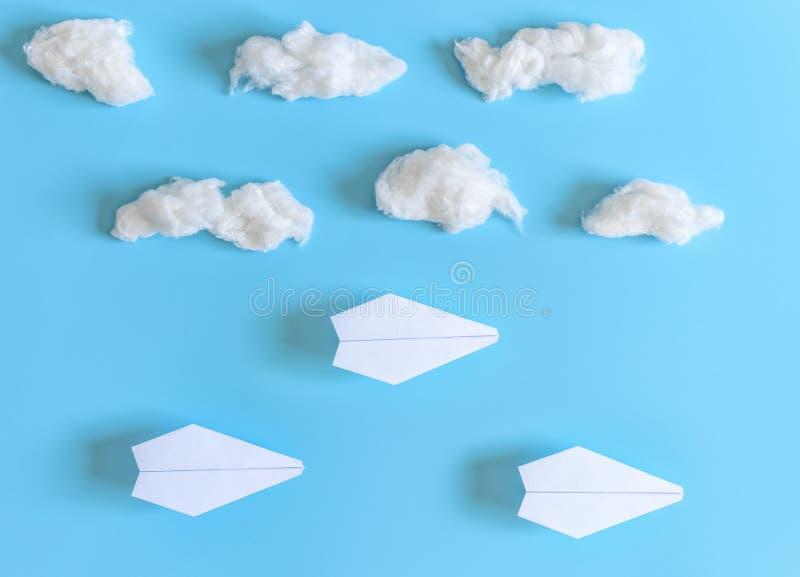 Tres aviones de papel de la papiroflexia entre las nubes blancas en fondo azul Copie el espacio para el texto imágenes de archivo libres de regalías