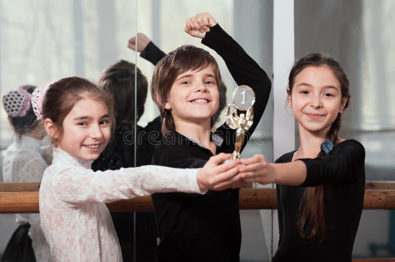 Los bailarines jovenes ganaron la taza fotografía de archivo