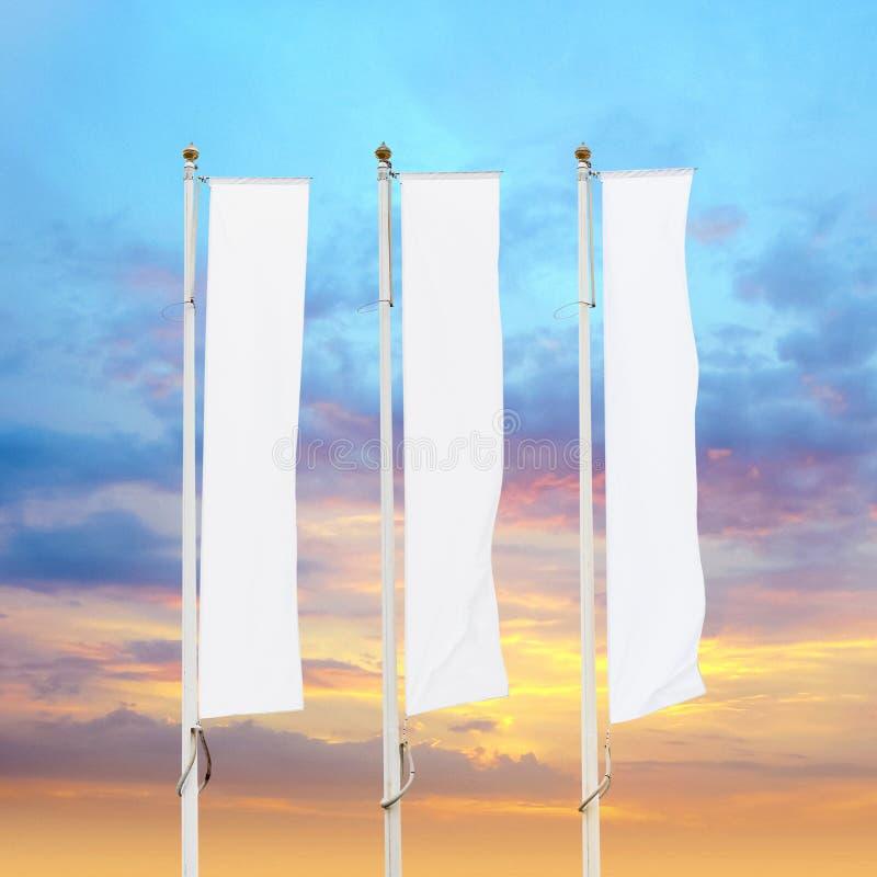 Tres banderas corporativas blancas en blanco con el fondo del cielo de la puesta del sol imagen de archivo libre de regalías