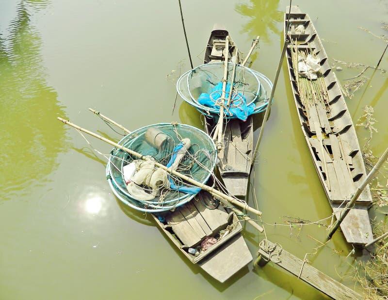 Tres barcos de madera antiguos en el canal con las herramientas de la pesca fotografía de archivo libre de regalías