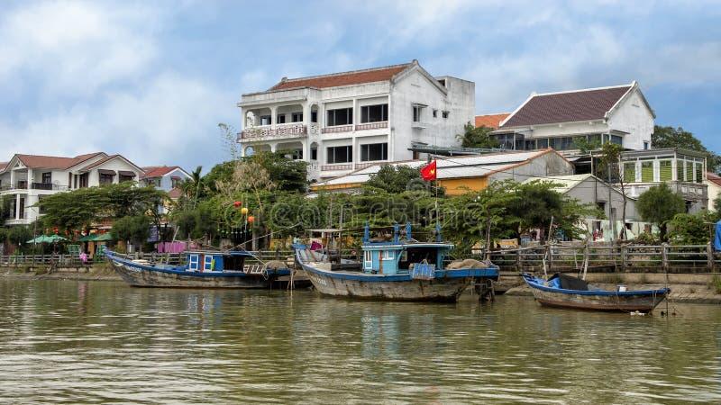 Tres barcos de pesca de madera a lo largo del banco de Thu Bon River en Hoi An, Vietnam, con el hotel en el fondo fotos de archivo