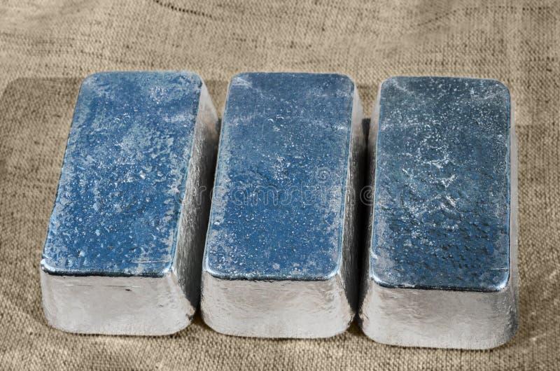 Tres barras de plata no marcadas contra una textura áspera de la materia textil imágenes de archivo libres de regalías