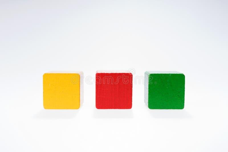 Tres bloques de los juguetes, ladrillos multicolores del edificio foto de archivo