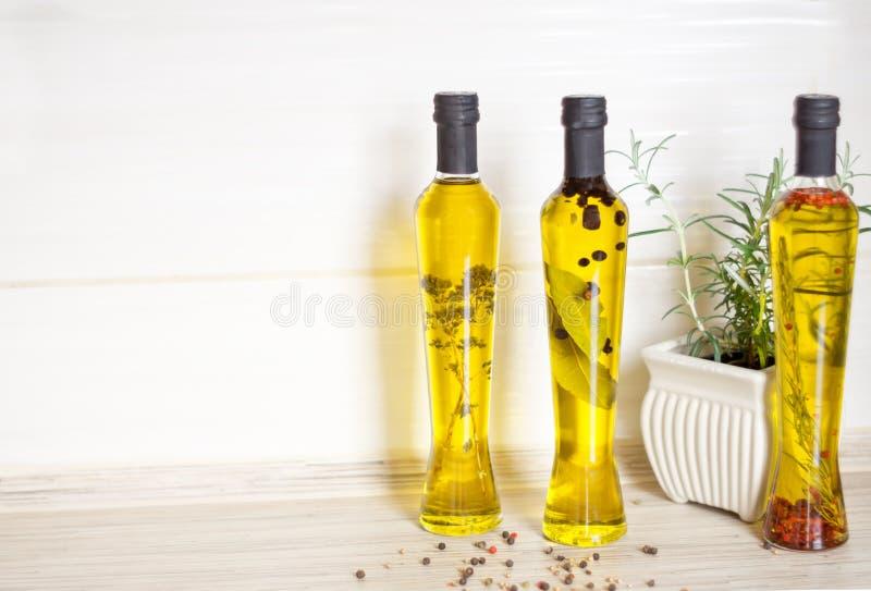 Tres botellas de aceite de oliva con las especias imagen de archivo