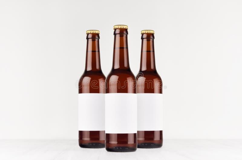 Tres botellas de cerveza marrones del longneck 330ml con la etiqueta blanca en blanco en el tablero de madera blanco, imitan para imágenes de archivo libres de regalías