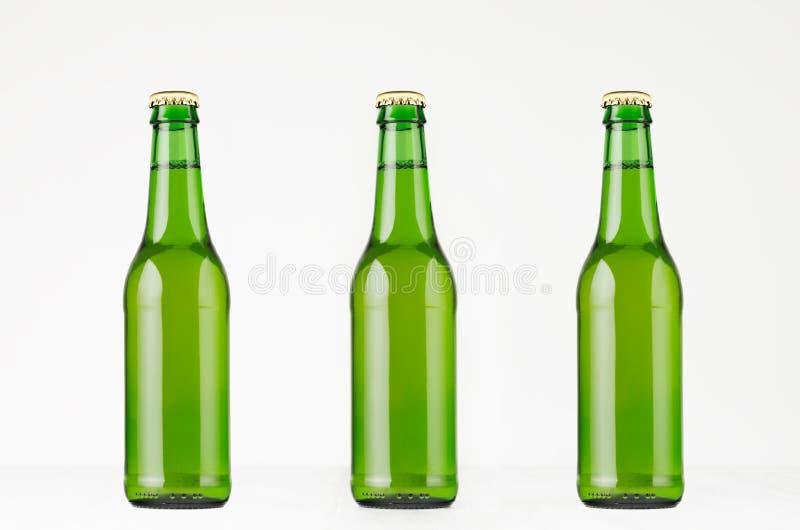 Tres botellas de cerveza verdes del longneck 330ml, imitan para arriba imagenes de archivo