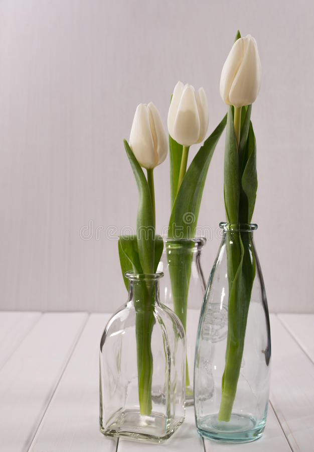 Tres botellas de cristal con los tulipanes fotografía de archivo