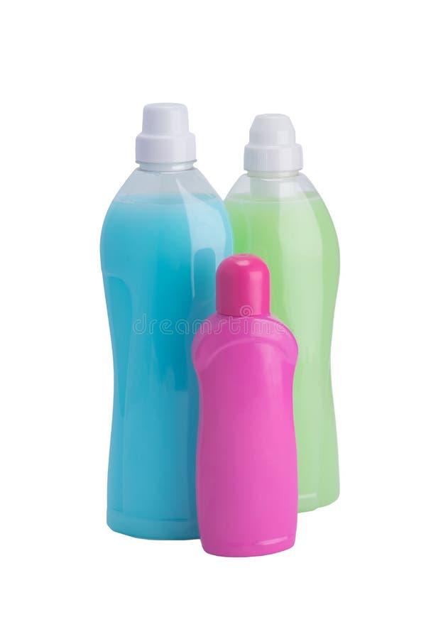 Tres botellas de detergentes para las telas que se lavan de diverso color, en un fondo blanco fotos de archivo