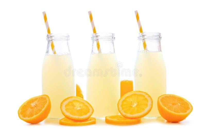 Tres botellas de limonada con las rebanadas y la paja del limón aisladas foto de archivo