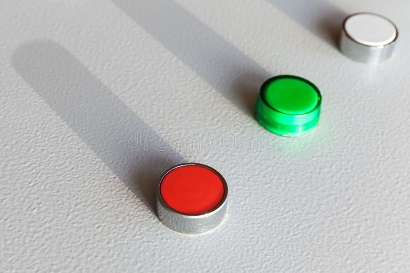 Tres botones industriales en panel de control gris imagen de archivo