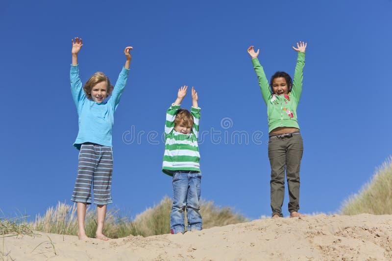 Tres brazos de los niños levantados divirtiéndose en la playa