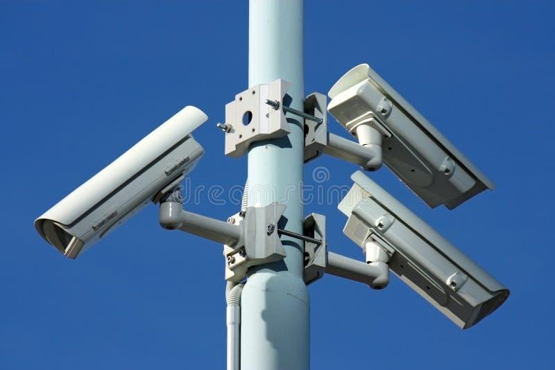 Tres cámaras de seguridad en poste de potencia imagen de archivo