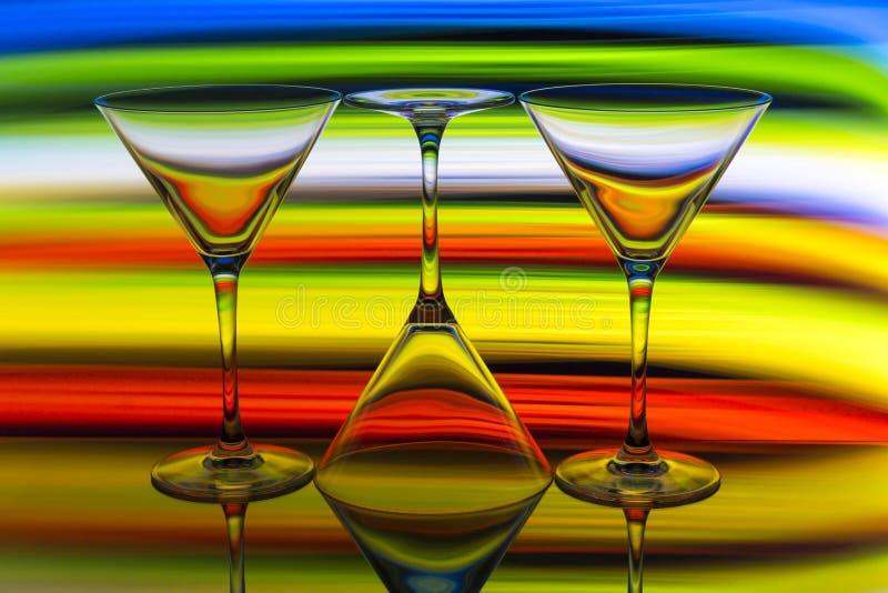 Tres cócteles/vidrios de martini en fila con un arco iris del color detrás de ellos imagenes de archivo