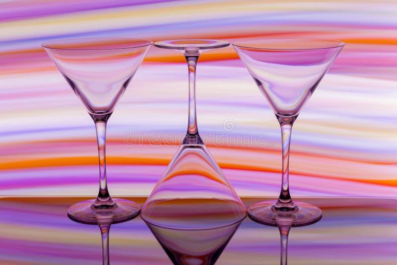 Tres cócteles/vidrios de martini en fila con un arco iris del color detrás de ellos foto de archivo