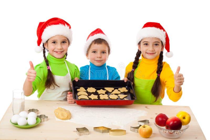 Tres cabritos sonrientes con cocinar de la Navidad imagen de archivo