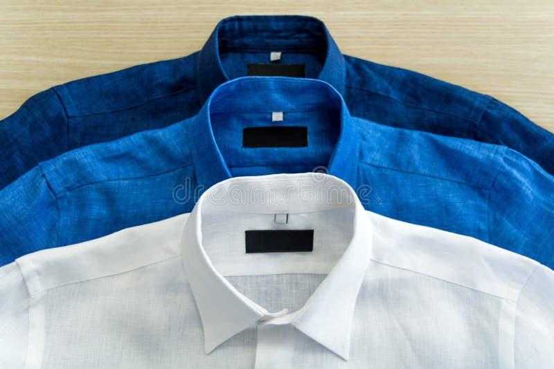 Tres camisas del ` s de los hombres en el color blanco, azul y azul marino imágenes de archivo libres de regalías